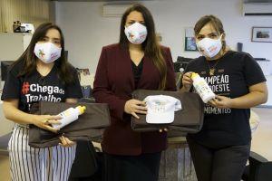 A juíza Karla Yacy (centro), juntamente com a procuradora-chefe do Ministério Público do Trabalho do Ceará, Mariana Ferrer, fazem a entrega de máscaras e brindes à assistente social do Ceará, Ana Cláudia Dias (dir)